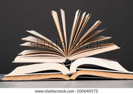 stacked open books on dark gray background