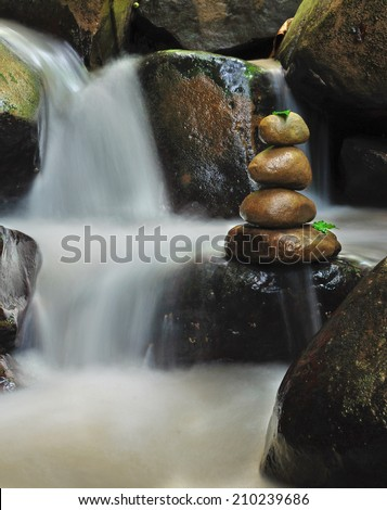 Stacked rocks on small stream creating a sense of peacefulness and tranquility. - stock photo