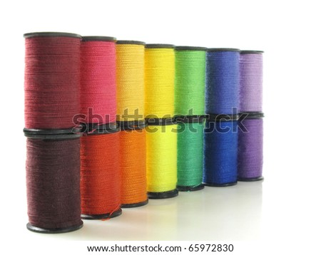 Stacked row of thread spools form a colorful spectrum - stock photo