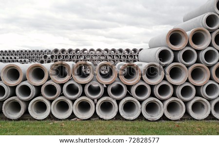 Stacked rows of concrete drainage pipes - stock photo