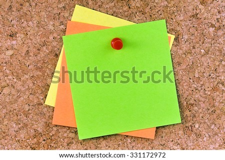 Stacked square blank postits affixed on cork board with red pushpin - stock photo