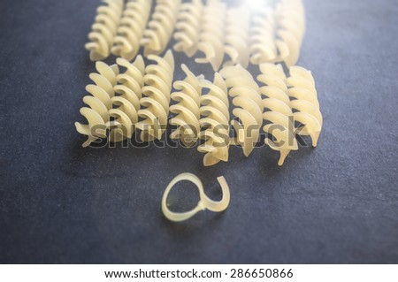 Stacked uncooked spiral pasta on a dark cloth background - stock photo