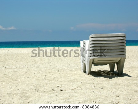 Stacked up beach loungers on a tropical beach