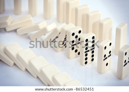 Stacked white dominoes falling over. - stock photo
