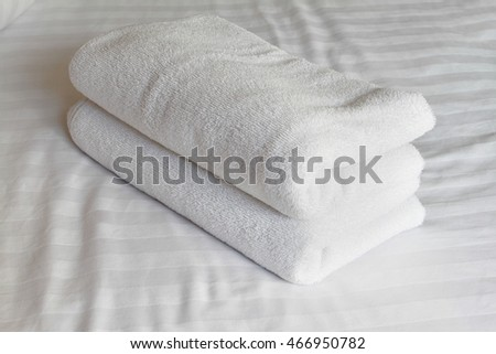 Stacked white spa cloth beach towels on white background.