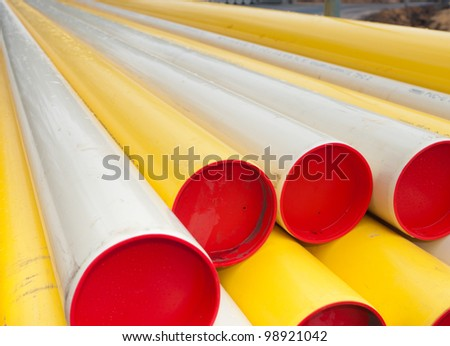 stacked yellow pvc pipes - stock photo