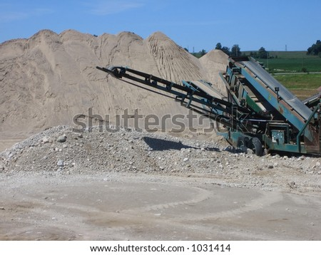 stacker - separates different sizes of gravel into piles at gravel pit - stock photo