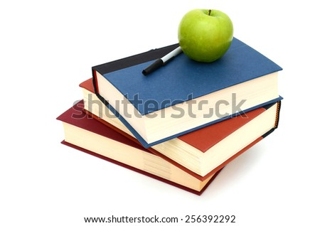 Stacking books with apple and pen - stock photo