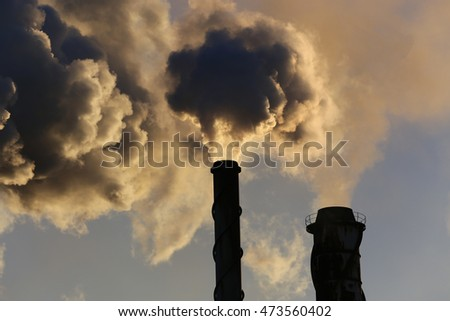 Stacks billowing smoke into blue skies.Industrial mine sites .Mine stacks or sugar cane mills and steam stacks. Smokestacks