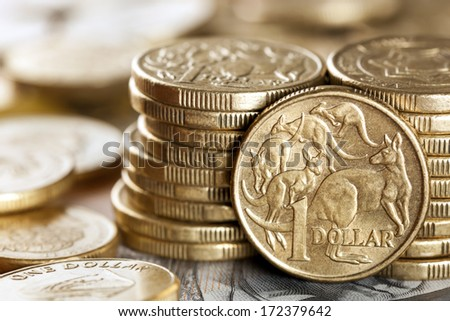 Stacks of Australian one dollar coins.  Focus on front coin. - stock photo