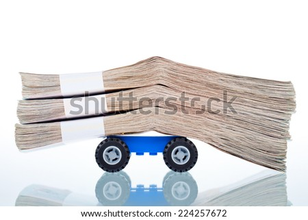 Stacks of banknotes on toy car wheels,on white background - stock photo
