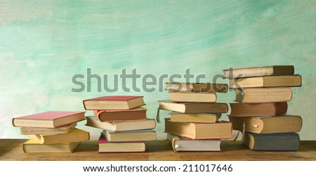 stacks of books, grungy background, free copy space  - stock photo