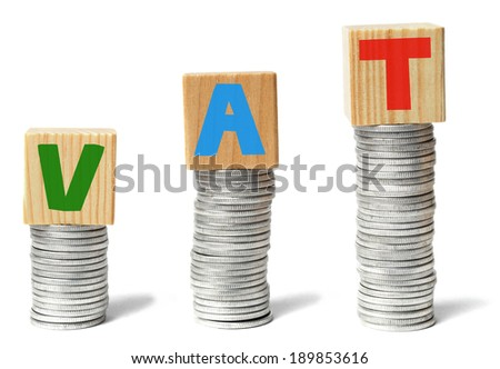 Stacks of coins and wooden blocks with letters VAT - stock photo