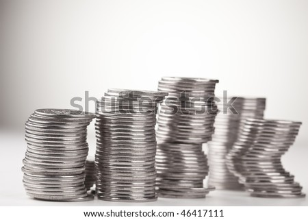 Stacks of coins, casting shadow on white.