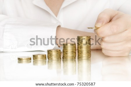 stacks of coins like diagram with reflection and hand put coin - stock photo