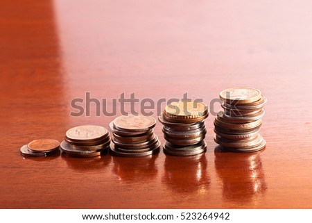 Stacks of coins of different heights on a varnished wooden table