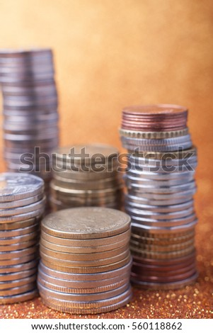 Stacks of coins on golden sparkle background. Financial concept