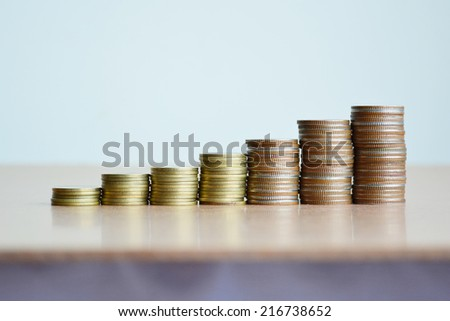 Stacks of coins on wooden background.