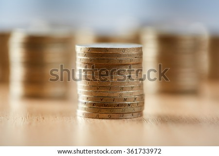 Stacks of coins on wooden table, with selective focus