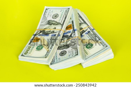 Stacks of $100 dollar bills isolated on green background.