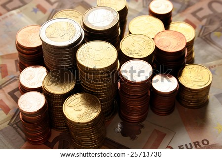 Stacks of Euro coins in front of fifty Euro banknotes