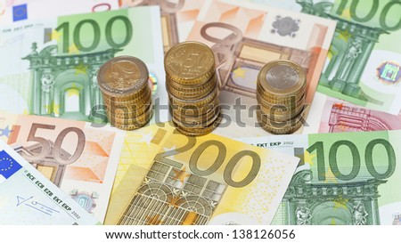Stacks of  Euro coins on banknote money background. - stock photo