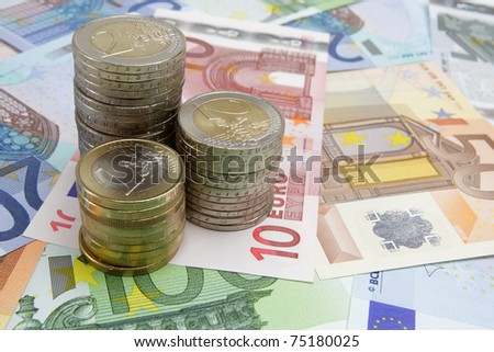 Stacks of Euro coins on Euro banknotes - stock photo