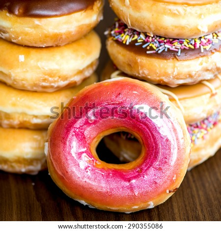 Stacks of Glazed Doughnuts with colourful sprinkles, chocolate, icing on top of them. Dark background. Selective focus. Narrow DOF - stock photo
