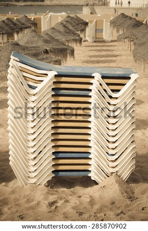 Stacks of loungers and thatched umbrellas on a sandy beach of Estoril. Portugal. Toned. - stock photo