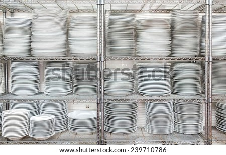 Stacks of many white plates on a wire rack shelf in a commercial kitchen - stock photo