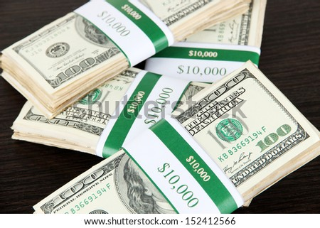 Stacks of money on wooden table - stock photo
