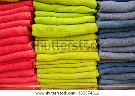 Stacks of multicolored towels on shelves