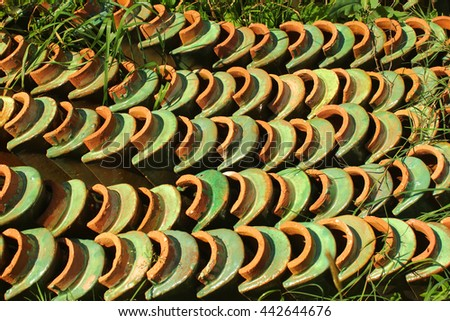 Stacks of old orange weathered roof shingles. Green glazed ceramic tiles are removed and piled in the grass - stock photo