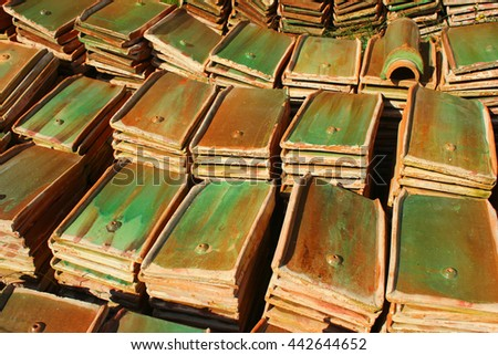 Stacks of old orange weathered roof shingles. Piles of green glazed ceramic tiles are removed - stock photo
