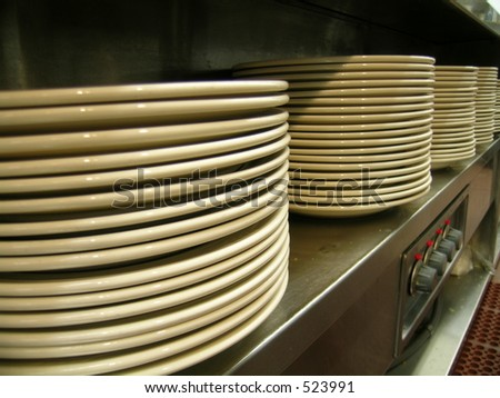 Stacks of plates ready for serving a meal in an institutional setting - stock photo