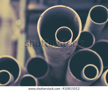Stacks of PVC water pipes. Abstract circular water pipe. Selective focus. Toned image. - stock photo
