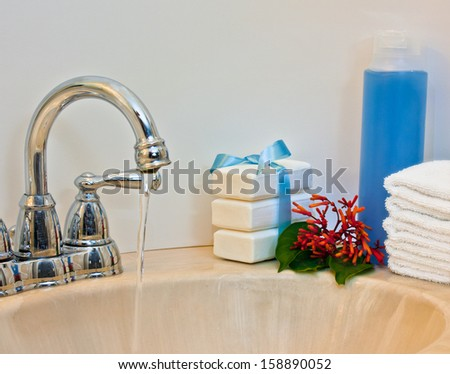 Stacks of towels and soap by a lavatory with water running. - stock photo
