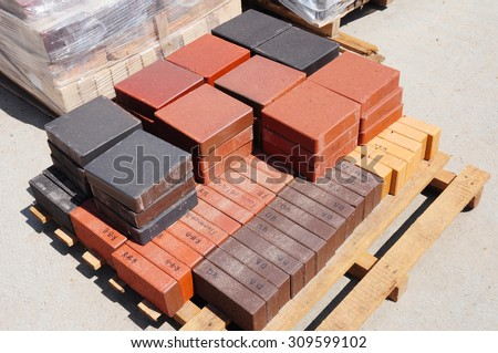 Stacks of various and for sale. Building and construction materials, colored concrete pavers (paving stone) or patio blocks organized on pallets for sale  - stock photo