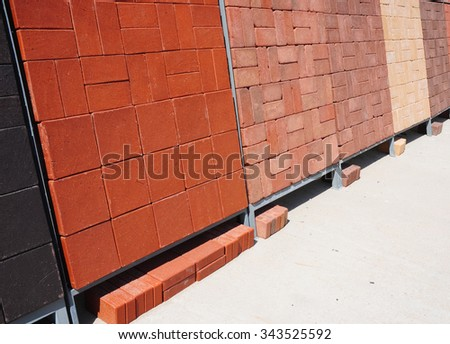 Stacks of various and for sale. Building and construction materials, colored concrete pavers (paving stone), bricks, and patio blocks organized on pallets for sale stored on metal shelves outdoors - stock photo
