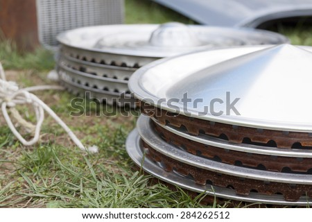 Stacks of vintage chrome hubcaps on the grass at a yard sale. - stock photo