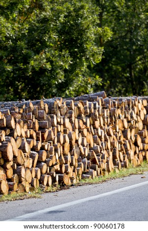 Stacks of wood by road. - stock photo