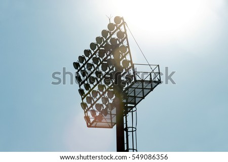 Stadium lighting poles in blue sky.