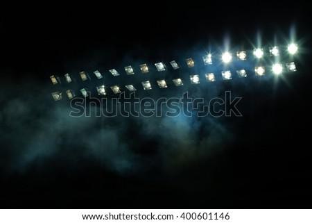 Stadium lights against dark night sky - stock photo