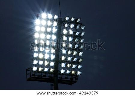 Stadium lights and dark blue sky - stock photo