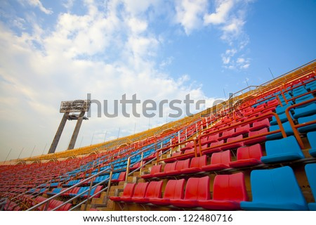 stadium place, red  and blue seats on stadium steps bleacher with spot light pole up bright sky - stock photo