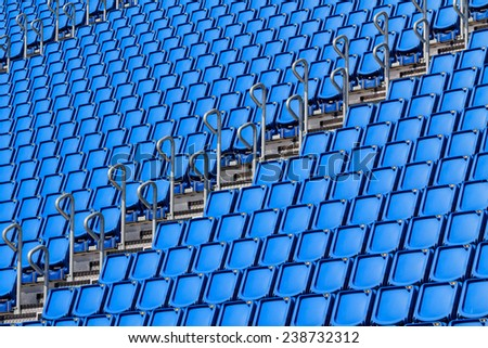 Stadium seating with blue folded up chairs - stock photo