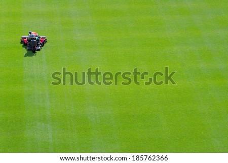 Stadium workers trim football field grass.  - stock photo