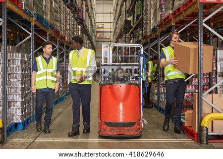 Staff at work in the aisle of a busy distribution warehouse - stock photo