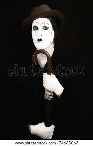 stage actor with makeup mime in a hat holding an umbrella in his hand