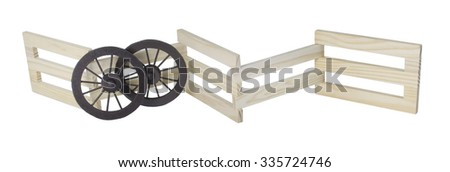 Stage Coach Wheels Against Wooden fence used to contain an area - path included - stock photo